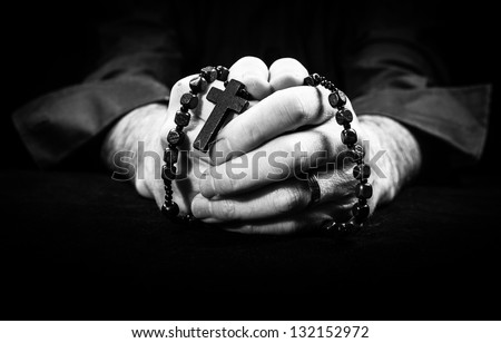 Hands holding rosary beads and cross while praying. - stock photo
