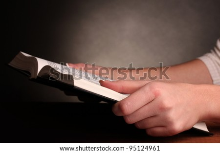 Hands holding russian holy bible - stock photo