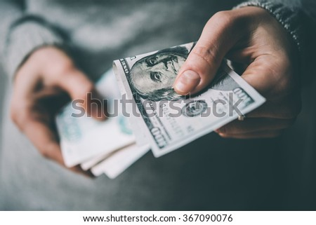 Hands holding russian rouble and us dollar bills. Toned picture - stock photo