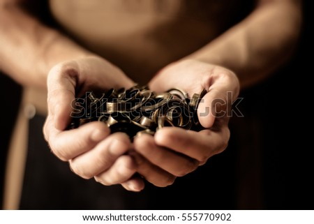 Hands holding set of cringles. Man manufacture concept