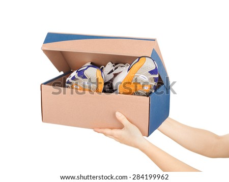 hands holding shoes in a box isolaterd on white