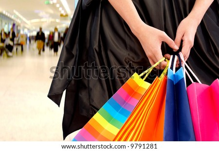 hands holding shopping bags in a shopping center - stock photo