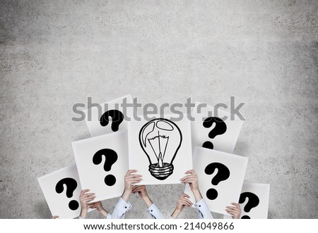 Hands holding sketch of lightbulb and question mark - stock photo