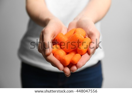 Hands holding small baby carrots, close up