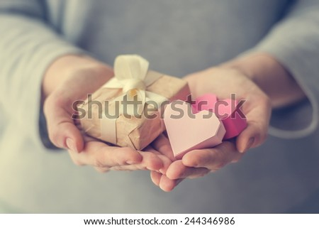 Hands holding small paper gift box and two paper valentine's hearts. Toned picture - stock photo