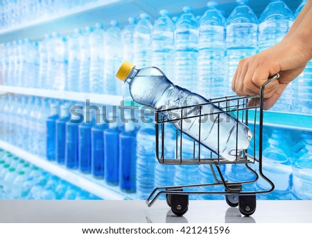 Hands holding small trolley with plastic bottle of water against background of shelves with bottles of water in supermarket                    - stock photo