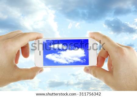 Hands holding smart phone on sky background