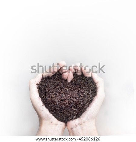 Hands holding soil of heart shaped. Love and protect nature. - stock photo