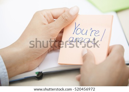 Hands holding sticky note with You are great text