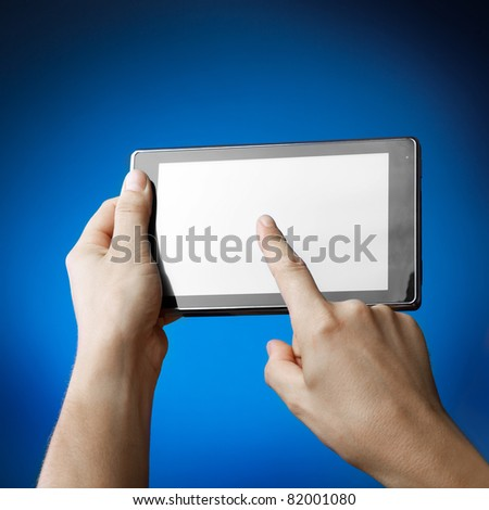 Hands holding Tablet PC on blue - stock photo