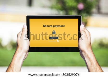 Hands holding tablet. Secure payment on the screen. Yellow background. - stock photo