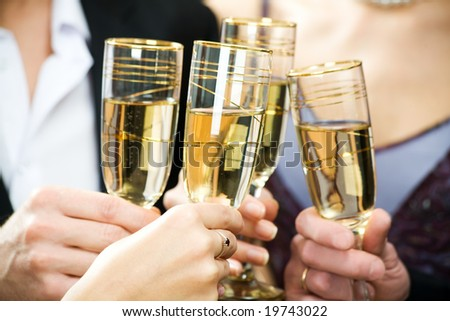 Hands holding the glasses of champagne making a toast - stock photo
