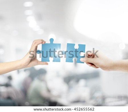 Hands holding the missing piece. Teamwork and partnership concept