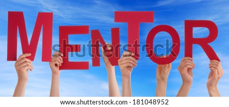 Hands Holding the Word Mentor in front of a blue Sky - stock photo