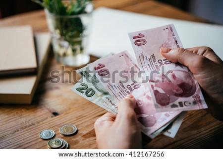 Hands holding turkish lira bills - stock photo