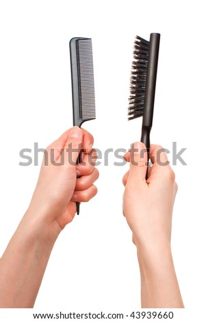 Hands holding two different hairbrushes isolated on white background