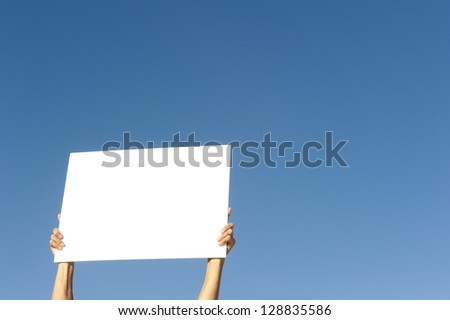 Hands holding white board sunny day outdoor, isolated with blue sky as background and copy space.