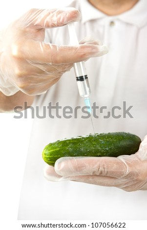 Hands in disposable gloves injecting cucumber with syringe over white background - stock photo