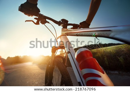 Hands in gloves holding handlebar of a bicycle - stock photo