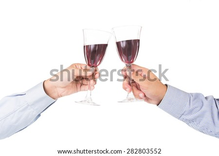 Hands in long sleeve shirt toasting red wine in crystal glasses