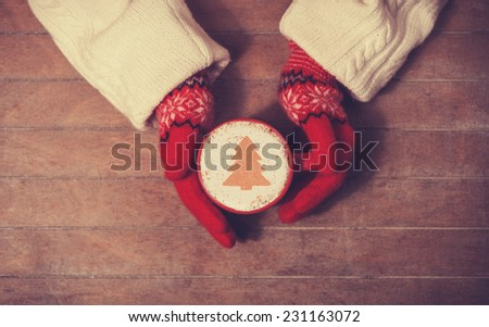 Hands in mittens holding hot cup of coffee. Photo in old color image style. - stock photo