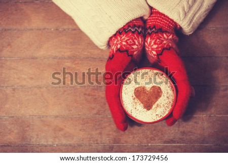 Hands in mittens holding hot cup of coffee. Photo with focus on heart. - stock photo