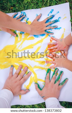 hands in paints on paper - stock photo