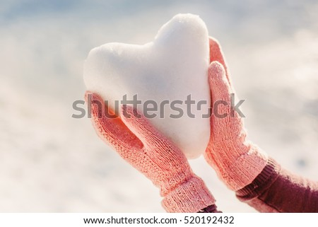 Hands in pink gloves holding snow heart. Winter and holiday time