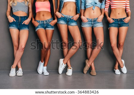 Hands in pockets. Close up of five women wearing jeans shorts and holding hands in their pockets while standing against grey background - stock photo