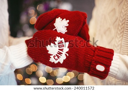 Hands in red gloves over the Christmas tree with Canada sign - stock photo