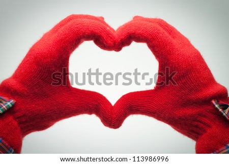 hands in red gloves show heart shaped sign over grey - stock photo