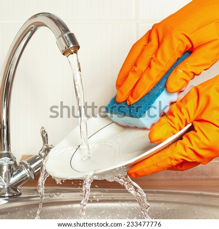 Hands in rubber gloves wash the dirty dishes under running water in the kitchen - stock photo