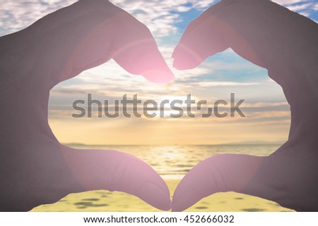 hands in the form of heart on blurred beach and beautiful sky with sun flare - stock photo