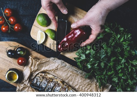 Hands in the process of cooking fish, pepper, parsley, tomato, lime on a cutting board on a black wooden background top view horizontal - stock photo