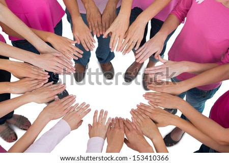 Hands joined in circle wearing pink for breast cancer on white background - stock photo