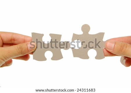 Hands joining two jigsaw pieces together
