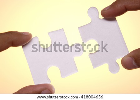 Hands joining two jigsaw puzzle pieces - stock photo
