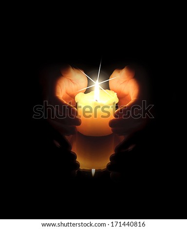 hands keeping the light of a candle - stock photo