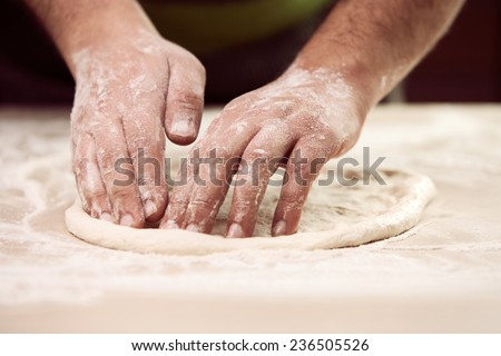 hands knead the dough ( Bot Mi ) for pizza making - stock photo