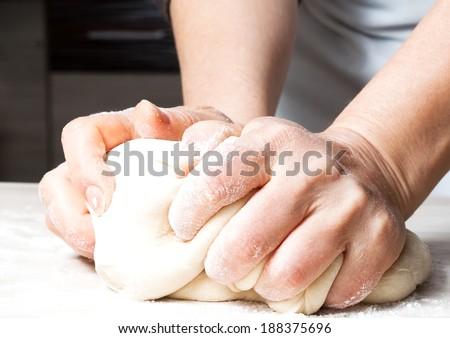 Hands kneading a dough - stock photo