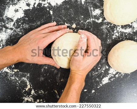 Hands kneading dough on black board with flour - stock photo