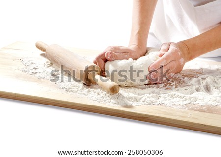 hands kneading dough on  board isolated on white background - stock photo