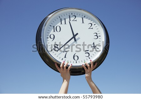 Hands lifting big clock outdoors
