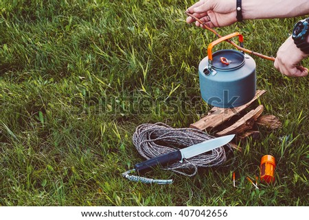 Hands lighting the fire at a campsite for cooking and making tea or coffee. Outdoor food items set. Travel, tourism and camping equipment. Picnic on the nature. Summer BBQ tools. Campfire kettle. - stock photo
