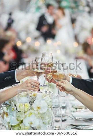 Hands linking glasses with white wine - stock photo