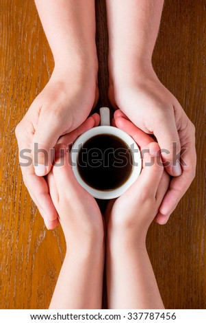 Hands loving couple and a cup of hot coffee top view - stock photo