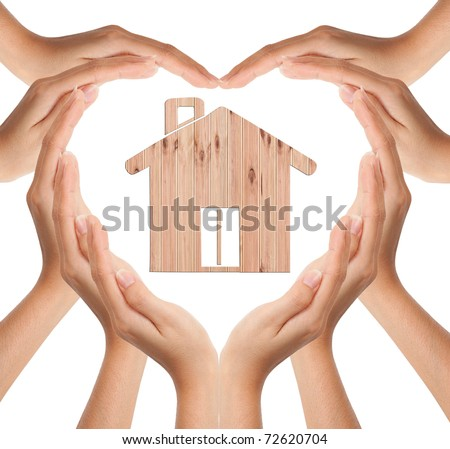 Hands make heart love shape with wood house - stock photo