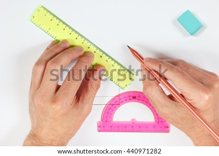 Hands making a drawing with pencil and ruler on a white sheet of paper - stock photo