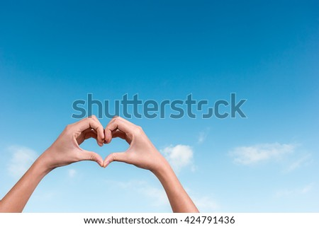 hands making a heart shape in the blue sky - stock photo