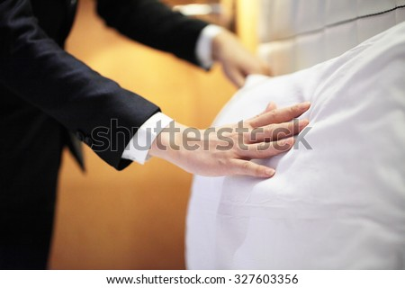 Hands Making Bed from Hotel Room Service - stock photo